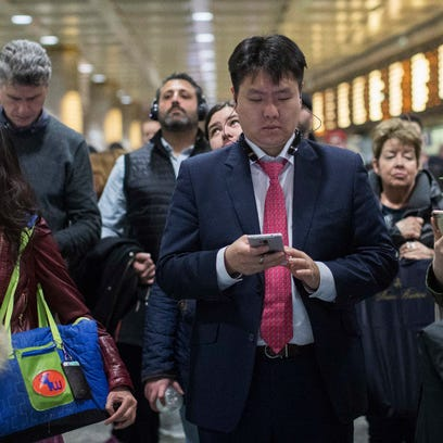 In this file photo, evening rush-hour commuters inspect
