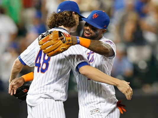 New York Mets third baseman Jose Reyes, right, embraces New York Mets starting pitcher Jacob deGrom (48) after deGrom pitched a complete game in the Mets 6-1 victory over the Chicago Cubs in a baseball game, Monday, June 12, 2017, in New York. (AP Photo/Kathy Willens)