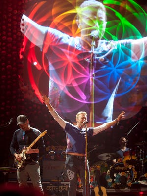 Chris Martin, lead vocalist and pianist for Coldplay is projected behind the band as he performs for a YUM Center audience. Members of the band include lead guitarist Jonny Buckland, Guy Berryman, bassist and Will Champion, drummer.27 July, 2016