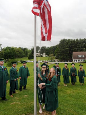 Kildonan School graduates Heather Feely, left, and Sophie Thorpe raise the flag, in school tradition, at the end of graduation ceremonies on Friday in Amenia.