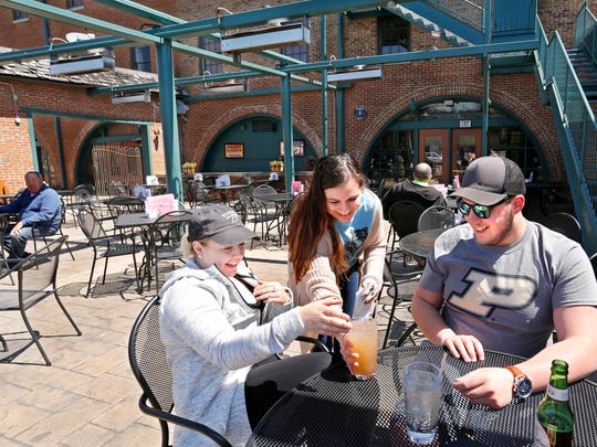 Stephanie Gorka serves up ice cold drinks for Katelyn Barr and Eston Clayton as they sit down to enjoy lunch on teh back patio at Sgt. Preston's of the North Thursday, April 26, 2018, 1204, 6 N. Second Street in downtown Lafayette.