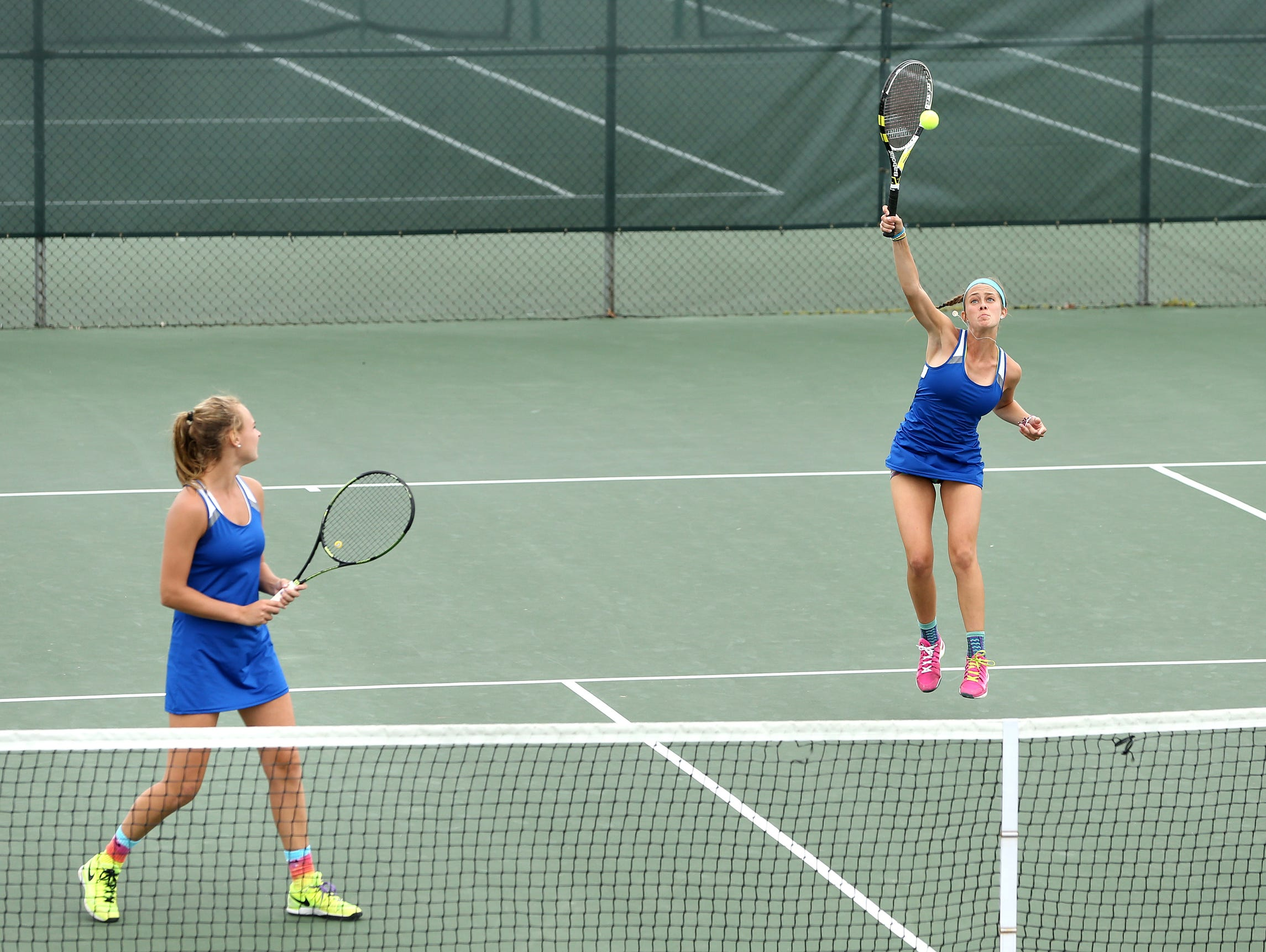 Carmel doubles players Emma Love, right, serves while teammate Lauryn Padgett watches.