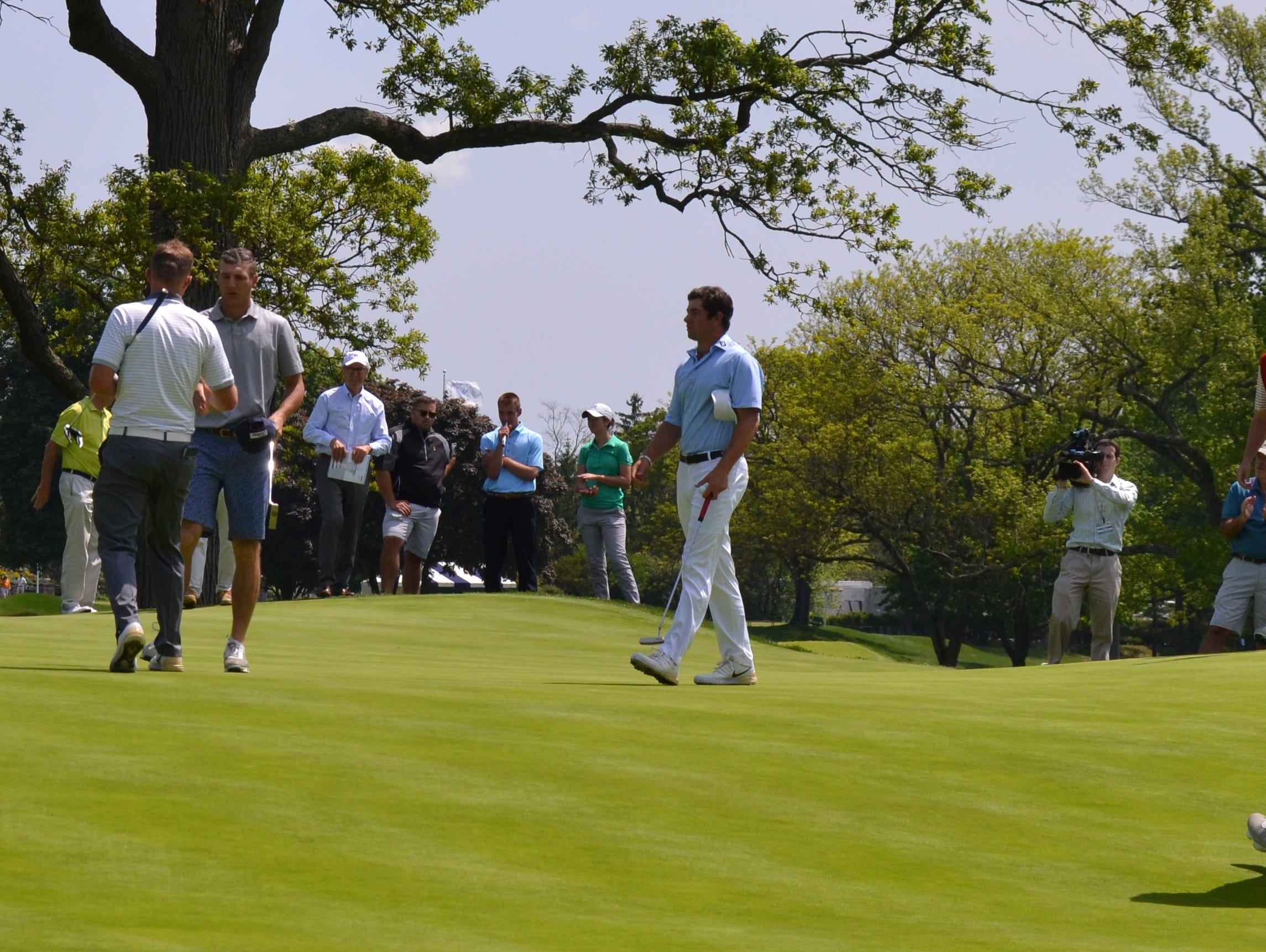 Paul McBride (left) and Garrett Rank shake hands while Cameron Young and Patrick Christovich approach to do the same after their Round of 32 match on Monday at the U.S. Four-Ball Championship at Winged Foot.