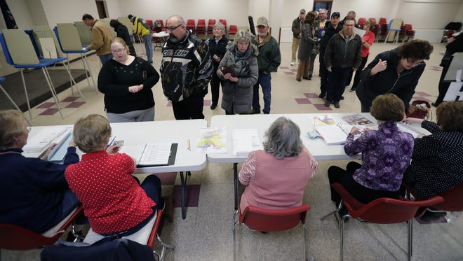 Voters line up Tuesday morning to vote in the community room at the old municipal building in Kaukauna.