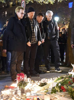 Irish band U2 (From L) lead singer Bono, guitarist The Edge, drummer Larry Mullen Jr and bass player Adam Clayton pay homage to attacks' victims near the Bataclan concert hall on November 14, 2015 in Paris, a day after a series of coordinated attacks in and around Paris.