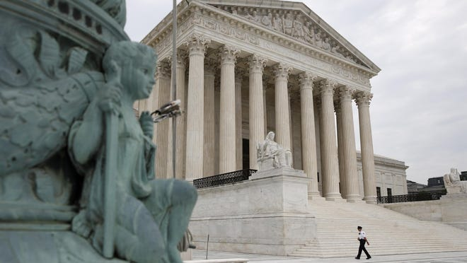 A police officer walks outside the Supreme Court on Capitol Hill in Washington on July 6. Two days later, the court issued its latest ruling on the contraception mandate in the Affordable Care Act.