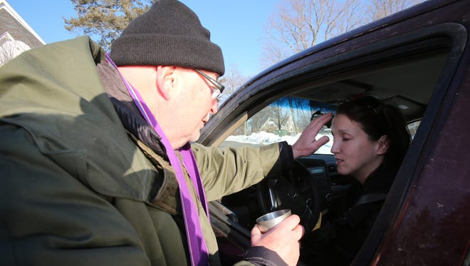 Erin Modafferi of Pleasantville receives ashes from the Rev. Daniel Ramm at a drive-thru Ash Wednesday service at Clarkstown Reformed Church.