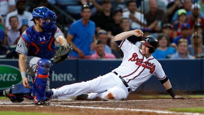 Atlanta's Chris Johnson, right, scores on a Mike Minor base hit as the Mets' Travis d'Arnaud handles the late throw in the fourth inning in Atlanta on Tuesday.