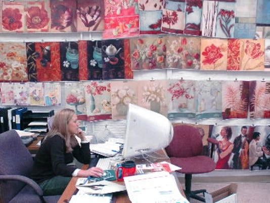 """In this 2006 photo, an employee at York Wallcoverings works inside a colorful space lined with samples of wallpaper. The owners of the York-based firm, Carl and Brenda Vizzi, were recently featured in a summer issue of """"Better Homes and Gardens."""""""