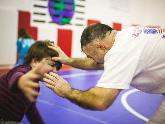 Joe Ramsey works with his son Joey inside Ramsey's International School of Wrestling shed in Mosinee.