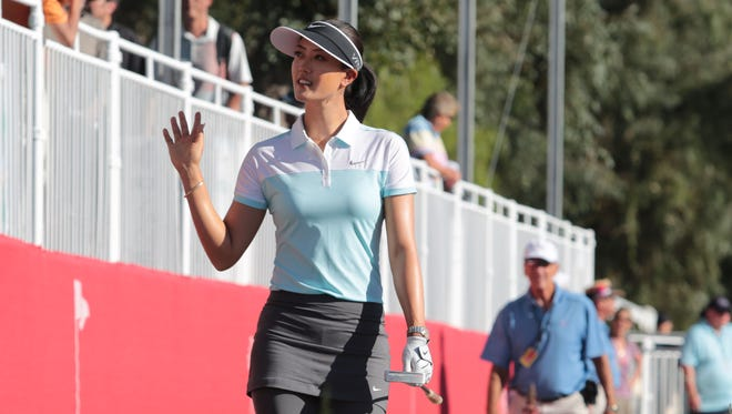 Michelle Wie waves to the grandstand on 18 during the first round at the Kraft Nabisco Championship on Thursday at Mission Hills Country Club.