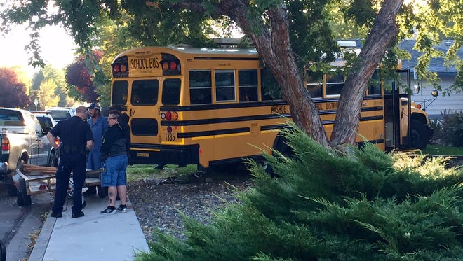A school bus is seen on a Sparks resident's yard after reportedly swerving and crashing into two parked vehicles Tuesday morning along Shadow Lane near Sparks Boulevard.