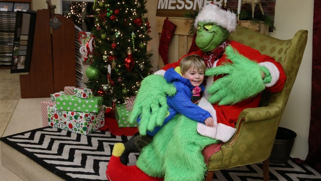"Adam Shelley, 3, Perinton, runs and hugs The Grinch, who was visiting with families at Messner Carpeting at the annual Candlelight Night in the village of Pittsford.  Peter Messner, store owner, said he's been taking part in the event for over 30 years.  ""This is being part of the community,"" he said.  ""It brings people into the community.  That's what it's all about, families having fun."""