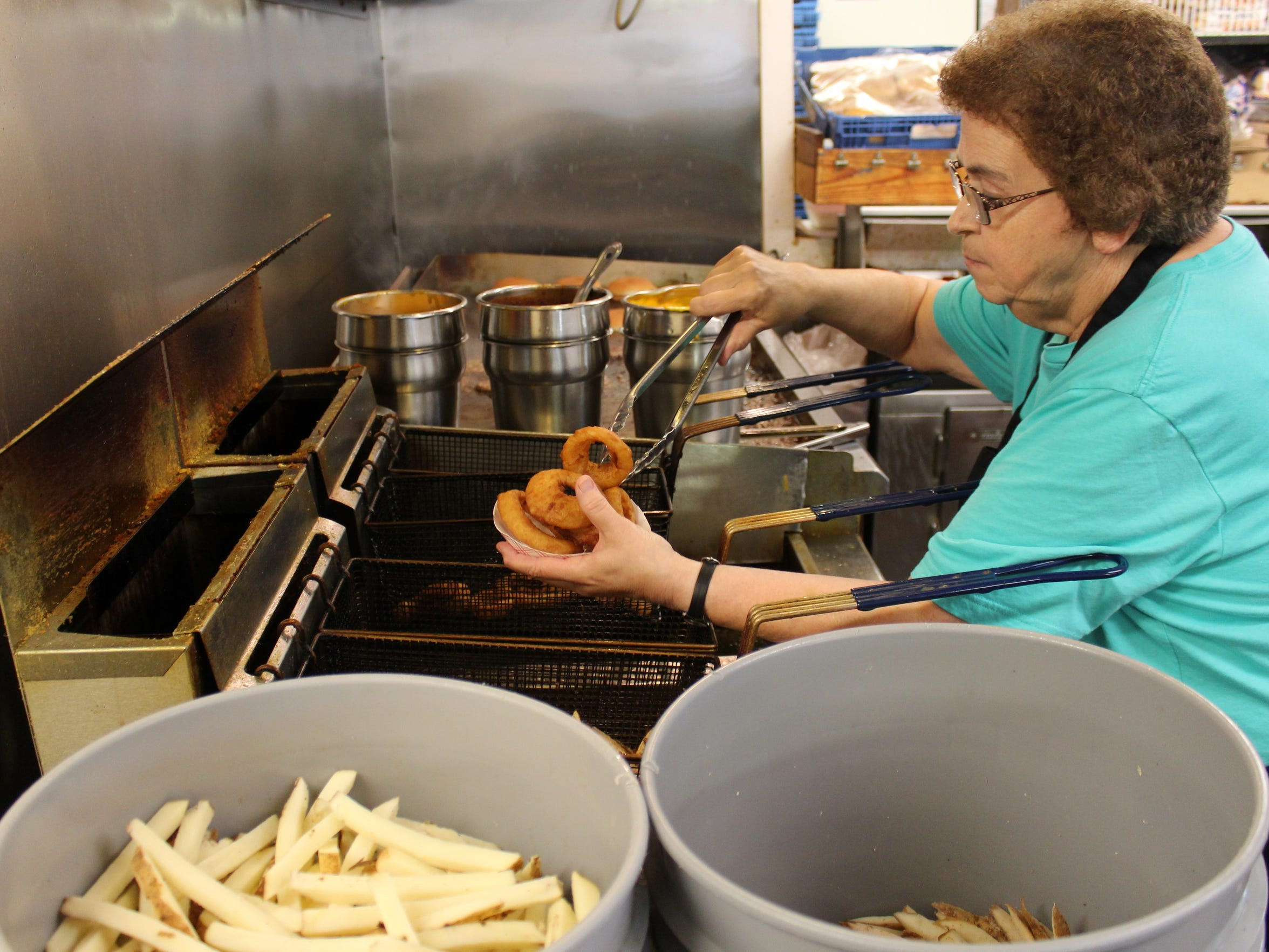 Pam Lee fills a tray with onion rings at Larry's Better Burger. She has worked at the northside drive-up restaurant for 21 years.