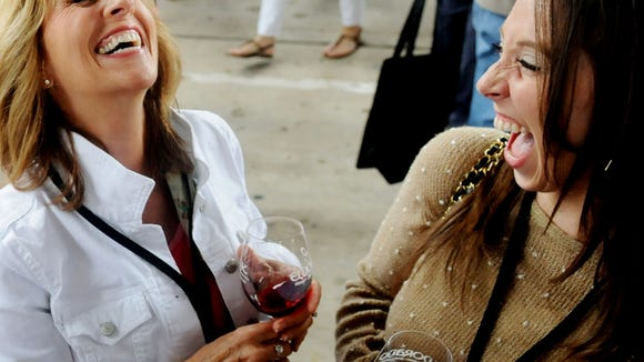 Suzy Sharp, left, and Carmen Walker enjoy a laugh Saturday afternoon during the CORK Wine Festival, a benefit for the Red River Revel, at Festival Plaza in downtown Shreveport.