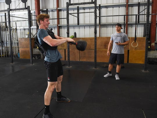 Ethan Elwell, 17, trains with his coach, Caleb Baretto, at Unified in Tamuning in this file photo. Elwell is competing at the Reebok CrossFit Games 2018 in Madison, Wisconsin, and is ranked No. 2 headed into the final tests.