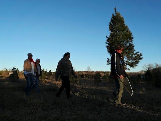 Jonathan Kuhl, 13, carries the family Christmas tree