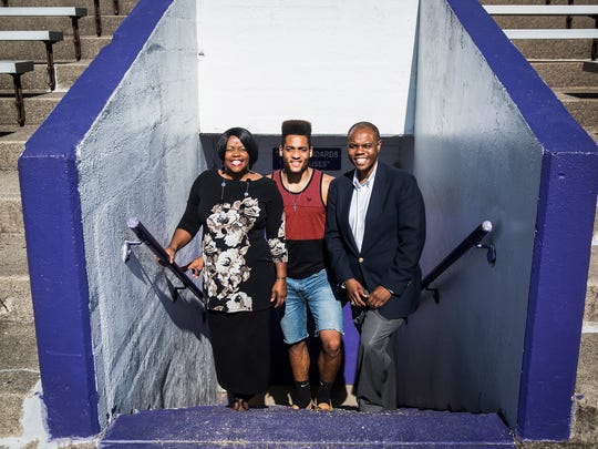 Central graduate Nahshon Prater with Jeanine Lee and Aaron Lake at the school's stadium Wednesday.