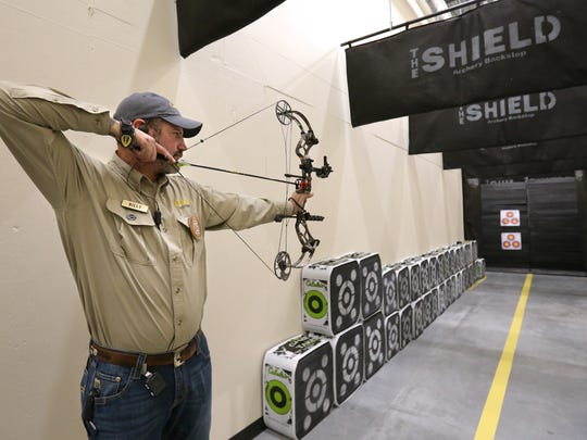 Cabela's archery tech Billy Meeks takes aim in the store's indoor archery range. The store opens on September 14.