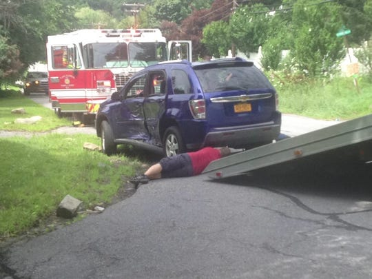 Worker gets a battered SUV ready for towing onto a flatbed after a two-SUV collision on Route 311 in Lake Carmel, July 17, 2014