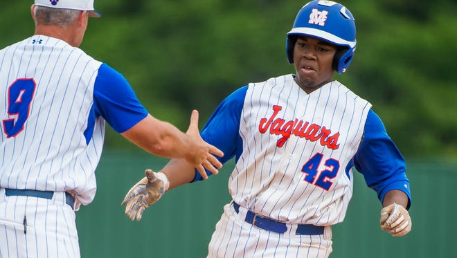 Madison Central third baseman Khristian Washington is congratulated by head coach Patrick Robey following a three run home run against Jackson Prep Saturday in Madison. (Bob Smith-For the Clarion Ledger)