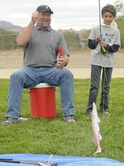 Fernley Intermediate School fifth-grader Jason Heinbruch reels in a catch while learning to fly fish. Principal Rob Jacobson cheers him on.