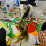 Anne Hooper, a senior at Holt High School, and other students paint a mural for the Holt Farmers Market Tuesday, March 3, 2015, at the market on Cedar Street. The murals were designed by students and will be displayed in the market building.