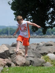 Caleb Drescher, 6, of Sheboygan, climbs on the rocks at Lakeside Park in Fond du Lac, while his family has a picnic Friday afternoon.
