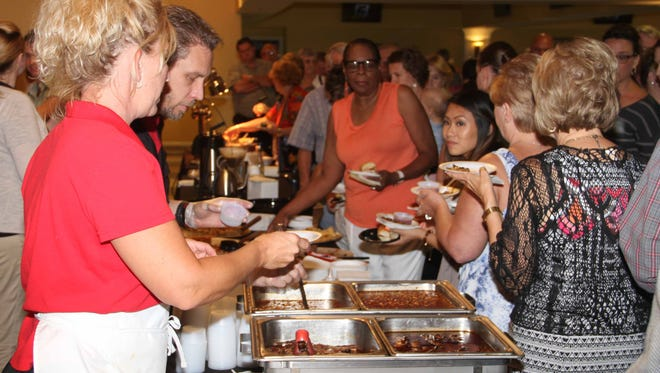 Attendees go through the line to taste various South Louisville cuisine at a previous TOSL event