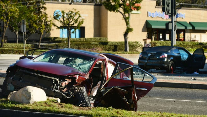 A Nissan sedan (left) and a Scion coupe remain in place hours following a crash that killed a Los Angles Police Department officer at the intersection of Cochran Street and Sycamore Drive in Simi Valley early Sunday morning.