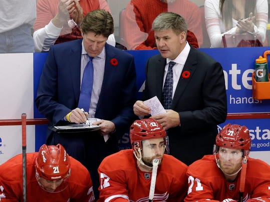 FILE - In this Nov. 9, 2013, file photo, Detroit Red Wings coach Mike Babcock, left, and assistant coach Bill Peters talk during the overtime period of an NHL hockey game against the Tampa Bay Lighting in Detroit. The Carolina Hurricanes have hired Peters as their new coach on Thursday, June 19, 2014. (AP Photo/Carlos Osorio, File)