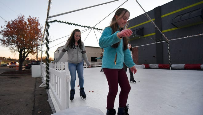 Sumrall sisters Jade, left, and Amber Breeland attempt to ice skate at the UpDown Trampoline Park on Thursday.