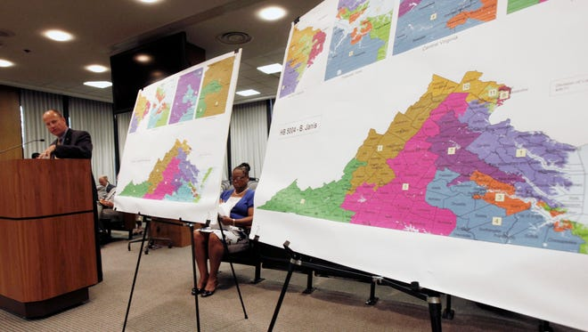 Del. William R. Janis, R-Henrico, at podium, presents his congressional redistricting plan to the Senate Privileges and Elections committee at the General Assembly Building in Richmond, Va., Thursday, June 9, 2011, as Sen. Mamie E. Locke, D-Hampton, who presented her own plan, sits between the two maps.