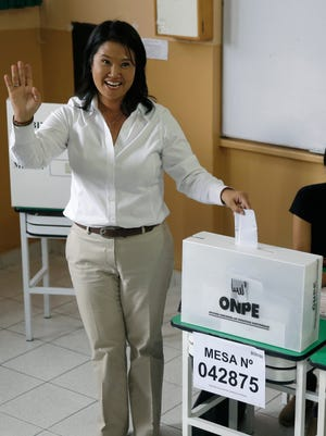 Presidential candidate Keiko Fujimori casts her ballot and waves for photos during general elections in Lima, Peru, Sunday, April 10, 2016. With the daughter of Peru's jailed former strongman the runaway favorite to get the most votes in Sunday's election, all eyes are on the race for second place and the right to face Keiko Fujimori in an expected presidential runoff. Also up for grabs on Sunday are all the seats in Peru's congress. (AP Photo/Martin Mejia)