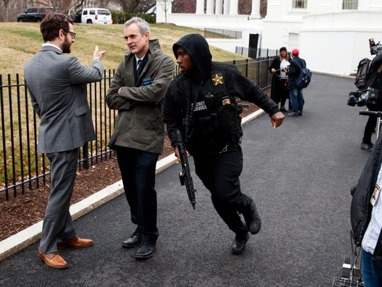 A Secret Service officer rushes past reporters after