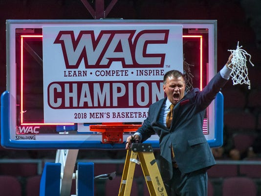 New Mexico State coach Chris Jans shows off the net he had just cut off after New Mexico State defeated Grand Canyon 72-58 in an NCAA college basketball game for the Western Athletic Conference men's tournament title Saturday, March 10, 2018, in Las Vegas. (AP Photo/L.E. Baskow)