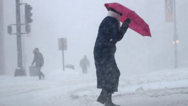 Cherie Burke contends with blowing snow during a blustery storm, Tuesday, March 14, 2017, in Portland, Maine. A late-season storm is hitting the Northeast, closing schools and prompting dire warnings to stay off the roads.