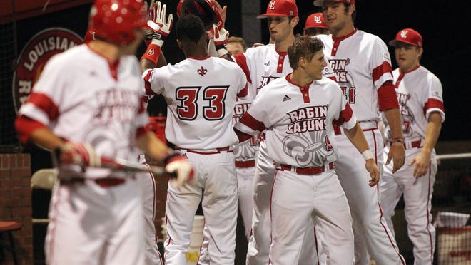 "UL's Jam Williams (33) is congratulated by teammates after stealing two bases in a row and scoring a run against Northwestern State in an NCAA baseball game Wednesday, March 4, 2015, at M.L. ""Tigue"" Moore Field in Lafayette, La."