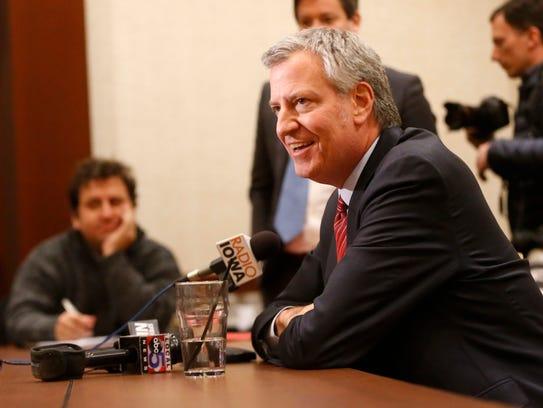 New York Mayor Bill de Blasio talks with members of