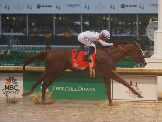 Mike Smith aboard Justify (7) crosses the finish line