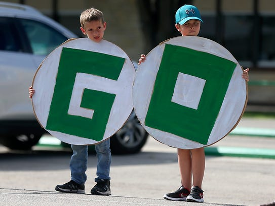 """Wall Elementary students hold up part of a """"Go Hawks"""""""