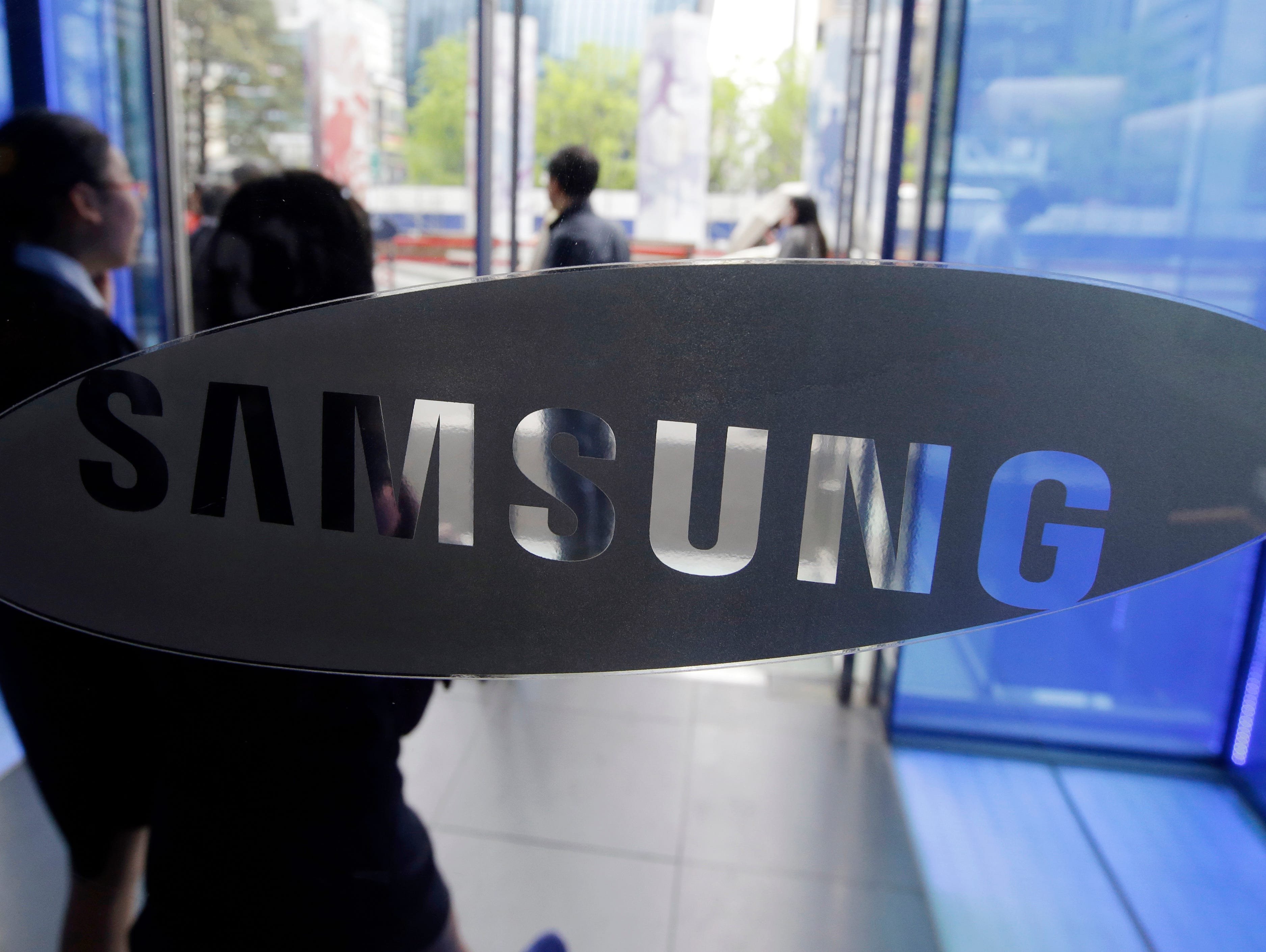 File photo taken in 2015 shows visitors walking by the Samsung logo at the company's showroom in Seoul, South Korea.