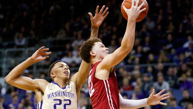Washington State guard Malachi Flynn (right) drives past Washington's Dominic Green to score in the Jan. 1 meeting between the rivals. WSU won that game in Seattle, 79-74.