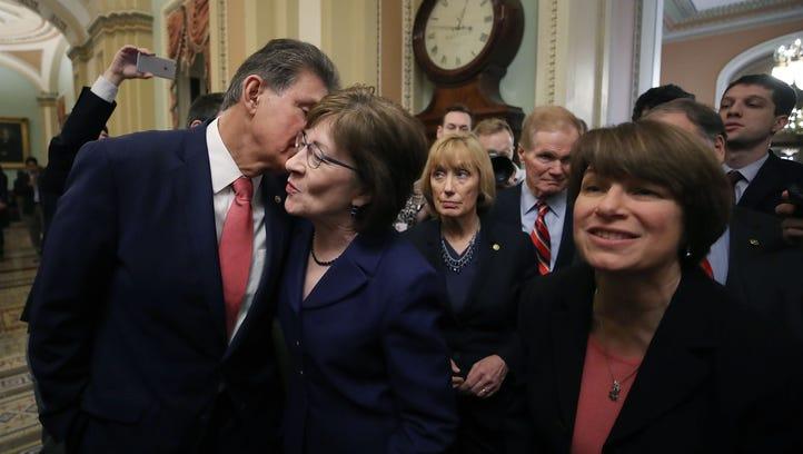 Sen. Joe Manchin (D-WV), (L), kisses Sen. Susan Collins