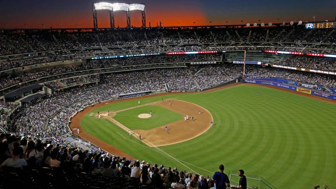 In this Aug. 29, 2019, file photo, the sun sets behind Citi Field during a baseball game between the New York Mets and the Chicago Cubs in New York. Major League Baseball players ignored claims by clubs that they need to take additional pay cuts, instead proposing they receive a far higher percentage of salaries and a commit to a longer schedule as part of a counteroffer to start the coronavirus-delayed season.