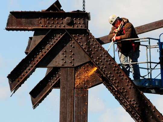 A worker cuts through steel beams while tearing down