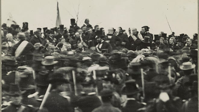 This photo shows part of the crowd gathered for the dedication of the Soldiers' National Cemetery in Gettysburg, Pennsylvania., where President Abraham Lincoln gave the Gettysburg Address. Lincoln is visible facing the crowd, not wearing a hat, about an inch below the third flag from the left.