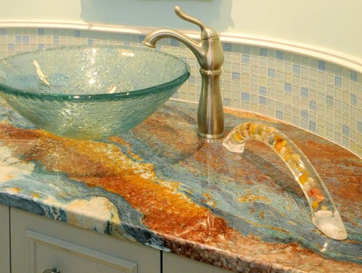 This photo provided by Best Bath Systems shows a Great Grabz Heritage multi-stone brown counter with grab bar in a bathroom.  Best Bath Systems has a series of acrylic towel bars with hidden mounts that come in more than two-dozen colors; some opaque, some translucent, some with embedded stones and some that even glow in the dark. (AP Photo/Best Bath Systems)