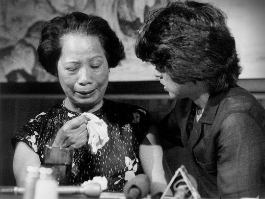 Lily Chin, left, is comforted by Helen Zia, President