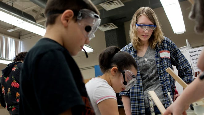 Northern student Abbey Kern, 17, watches as Crull Elementary third-graders Max Daniels, 9, and Mariahm Meadows, 8, write their observations as they do an experiment testing heat retention in different materials.